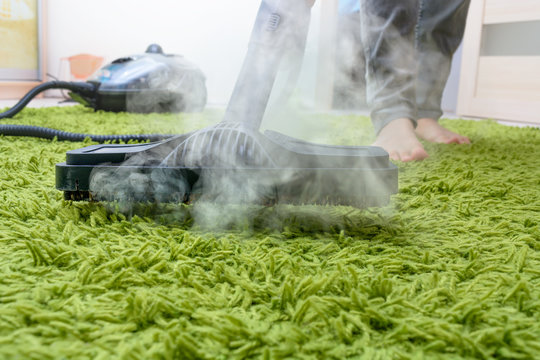 woman cleans a carpet with a steam cleaning. getting rid of dust mites