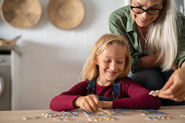 Grandmother and grandchild solving jigsaw puzzle