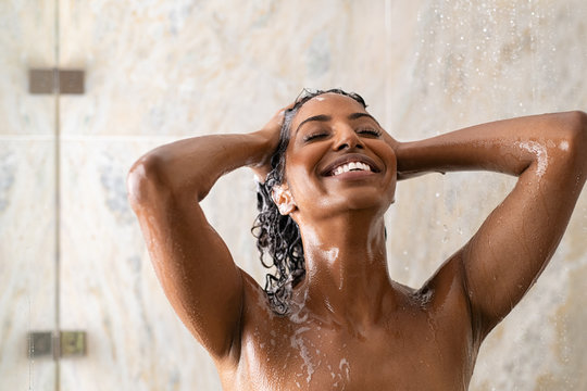 African woman washing hair under shower