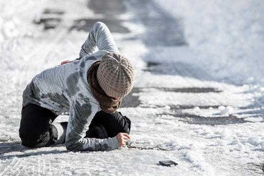 Frau hält sich den Rücken, Sturz und Verletzung durch Glatteis und Schnee