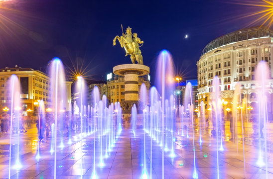 Square Macedonia in Skopje at night with dancing illuminated fountains and statue of Alexander the Great (warrior on horse) at background