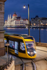 Budapest, Hungary - Yellow tram on the move at Clark Adam Square with illuminated Parliament building at background at blue hour