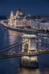 Budapest, Hungary - The world famous illuminated Szechenyi Chain Bridge with the Parliament of Hungary and sightseeing boat on River Danube taken at blue hour