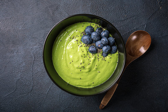Overhead shoot of breakfast detox green smoothie bowl from banana and spinach on black background. Healthy food concept with copy space, top view