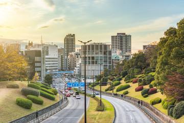 The edges of Akasaka Suginami Road lined with azalea shrubs trimmed into balls and separating Yoyogi Park from Yoyogi Olympic Gymnasium.