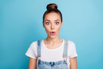 Portrait of impressed lady looking with opened mouth wearing white t-shirt denim jeans overall isolated over blue background