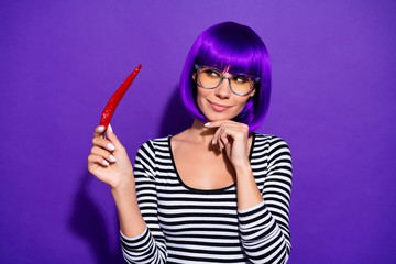 Portrait of lovely person holding pepper looking having thoughts dressed striped shirt isolated over purple violet background