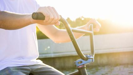 LENS FLARE Extreme biker holding bike handlebar grips with sun shining behind