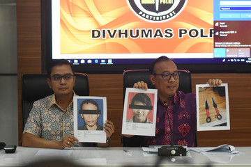 Indonesian National Police spokesman Dedi Prasetyo shows pictures of suspects and the knifes used for attacking Indonesia's chief security minister Wiranto in Jakarta