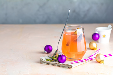 Christmas and New Year pink cocktail with fig and cinnamon  in glass on pink concrete background, close up, surrounded  holiday decor. Winter festive drinks and alcoholic cocktails or detox drink
