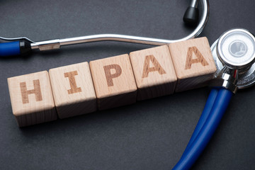 Wooden block form the word HIPAA (Health Insurance Portability and Accountability Act) with stethoscope. Medical concept.