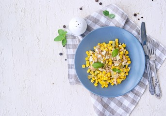 Salad with tuna, corn and pickled cucumber on a gray plate on a light concrete background. Tuna salad recipes. Top view.