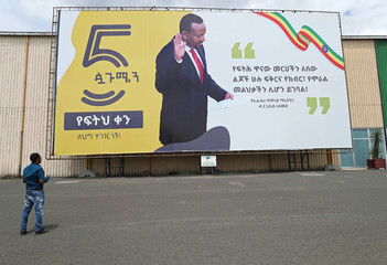 A man looks at a billboard with the image of Ethiopian Prime Minister Abiy Ahmed in Addis Ababa
