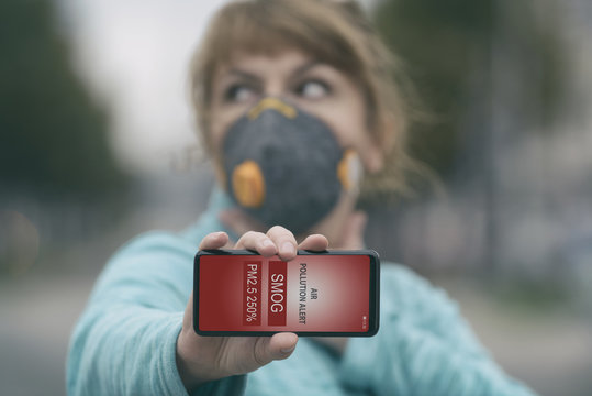 Woman wearing a real anti-smog face mask and checking current air pollution with smart phone app
