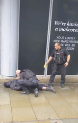 A police officer points a taser while the other holds a man down outside Arndale shopping center, where several people have been stabbed, in Manchester