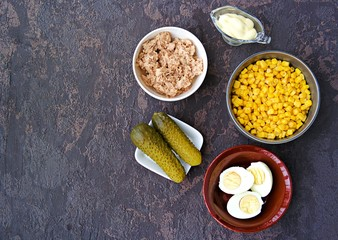 Ingredients for cooking salad with tuna and corn on a brown concrete background. Tuna Salad Recipes. Top view, copy space.