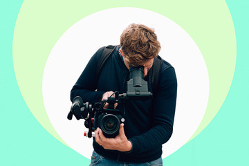 frontal portrait of a cameraman recording with a professional camera against a colorful digital background