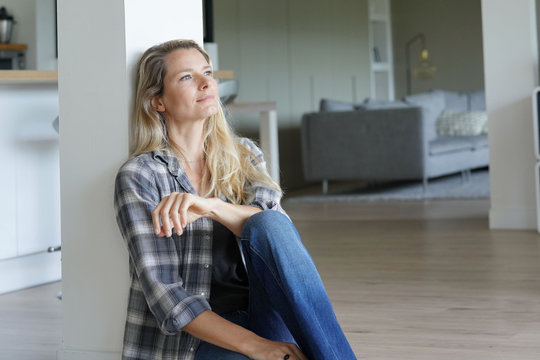 Beautiful blond woman relaxing at home, sitting on floor