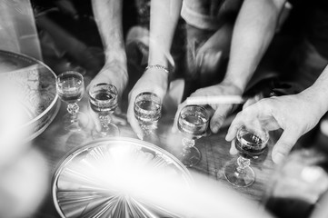 Black and white photo of people holding glasses of alcohol. Feast, spirits. Celebration. B-Day. Wedding day.