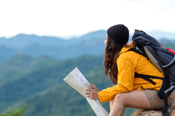 Asian women hiker or traveler with backpack adventure holding map to find directions and sitting relax on the mountain nature for destination leisure trips. Travel and Lifestyle Concept