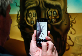 "A visitor takes a photograph of a painting by Spanish artist Dali during the exhibition ""Dali & Magritte"" in Brussels"