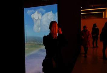 "A visitor takes a photograph of the ""Cloud Room"" during the exhibition ""Dali & Magritte"" in Brussels"