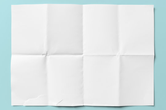 White paper folded in eight, isolated on light blue
