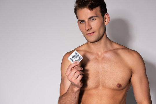 sexy and shirtless man holding condom and looking at camera on white