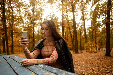 Beautiful girl takes pictures on the phone in the autumn park. Selfie. Wonder autumn. Lifestyle.