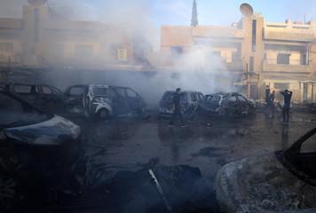 A man walks near burnt cars at the site of a car bomb blast in Qamishli