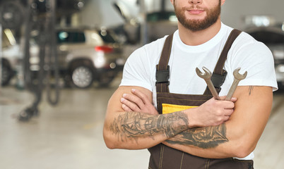 Male mechanic standing with folded arms and keeping wrench