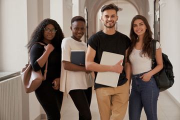 Four mixed-race students looking at camera in college hall