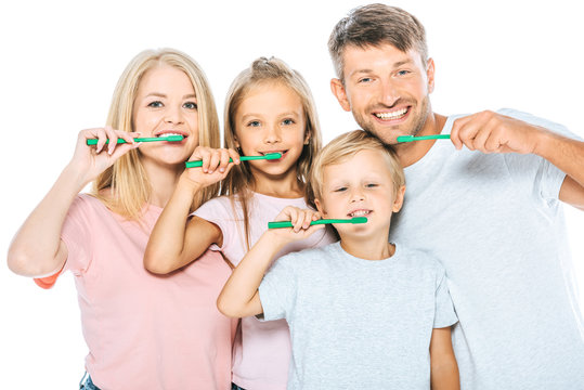 happy parents and children holding toothbrushes while brushing teeth isolated on white