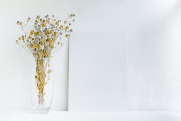 Mockup with a white canvas and dry flowers in a vase on a white table