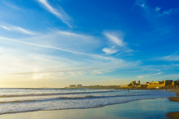 Sunset on the beach Santa Maria del Mar and Cadiz city view, Spain, Andalusia
