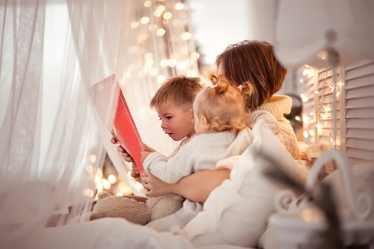 Mom reads a book to children on a cozy winter evening
