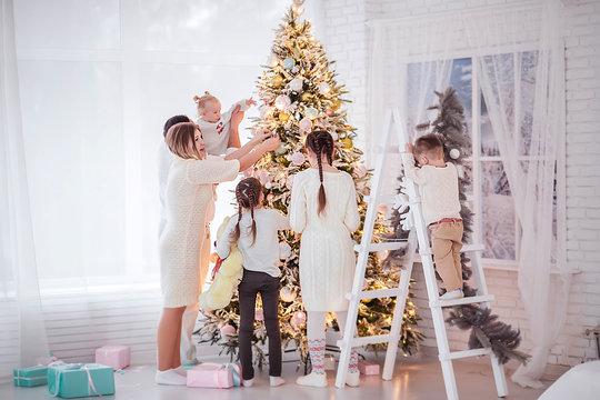 Big beautiful family decorates a Christmas tree