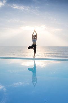 Asian woman practice yoga on the beach