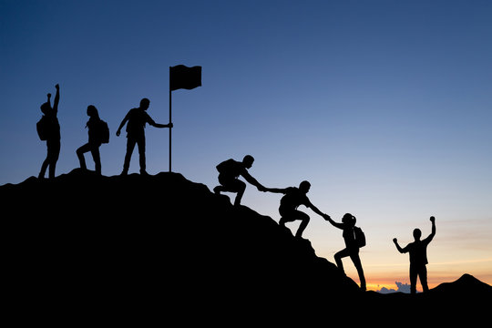 Silhouette of people helping each other hike up a mountain at sunset background. Teamwork, success and goal concept.