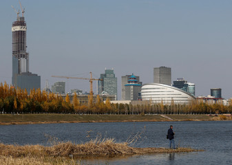 A man fishes on a bank of Ishim river against a backdrop of the downtown in Nur-Sultan