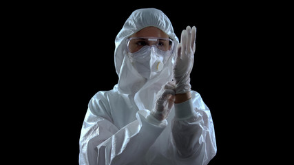 Person in protective suit wearing rubber gloves against dark background, toxins