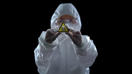 Scientist in protective suit holding poison symbol in hands, black background