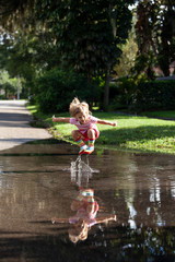 A little girl wearing rainbow rain-boots jumping and splashing in her reflection in a puddle