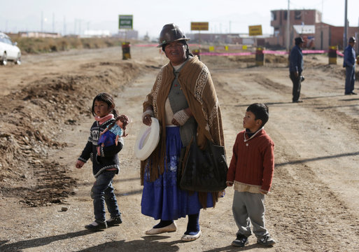 A woman with children are seen near the Institute of Nuclear Medicine and Cancer Treatment in El Alto