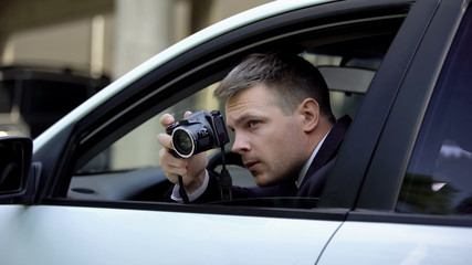 Male agent secretly taking photo by camera sitting in car, photojournalism