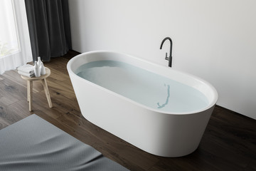 Top view of tub with water in wood floor bathroom