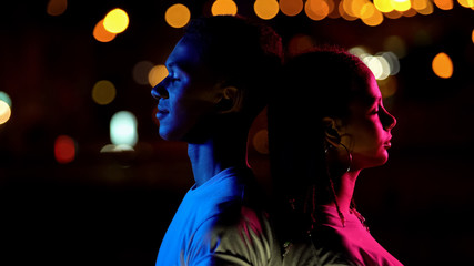 Boy illuminated by blue, girl in pink light at night, concept of man vs woman