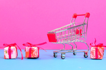 Shopping cart with gifts on multicolored background