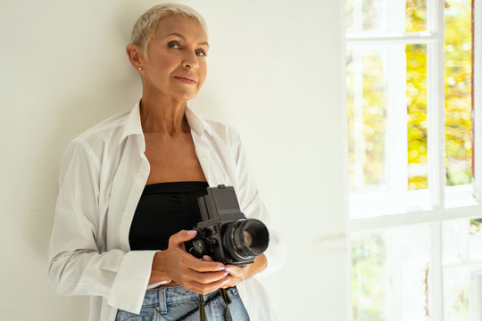 Cheerful blonde female person holding her camera