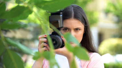 Suspicious female with camera hiding behind trees at park, spying husband